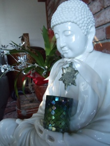 Buddha graces the fireplace holding a festive green candle.