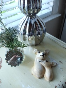 Gram's deer from her cabin grace the buffet table next to a vase filled with rosemary and pine cuttings.